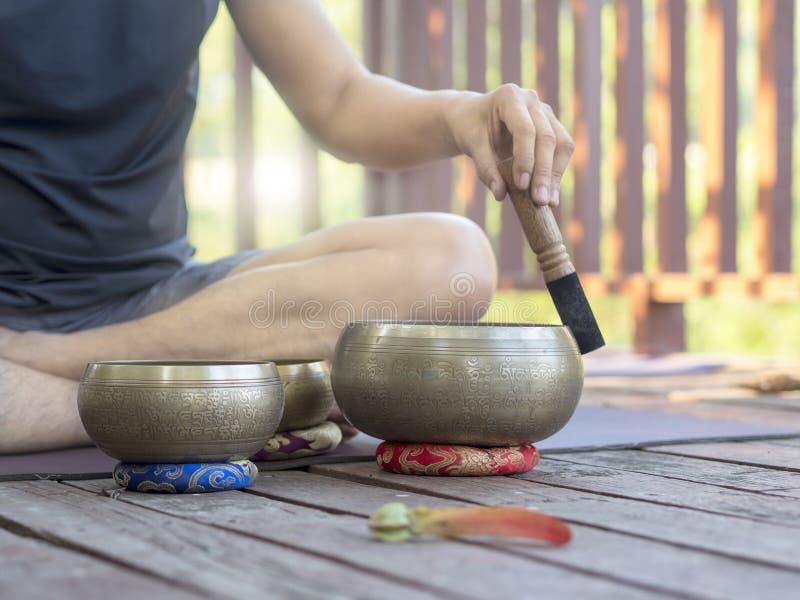 Deux hommes de yoga font le yoga extérieur avec des cuvettes de chant images libres de droits