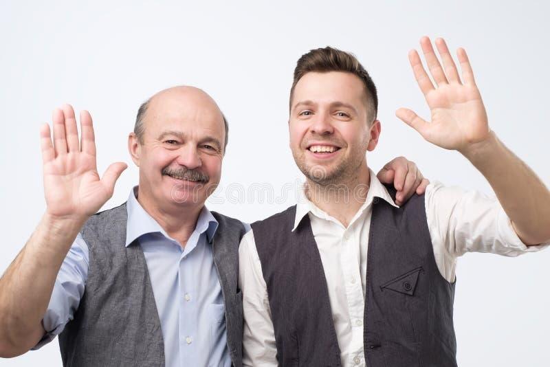 Deux hommes disant le bonjour, ondulant une main photographie stock libre de droits