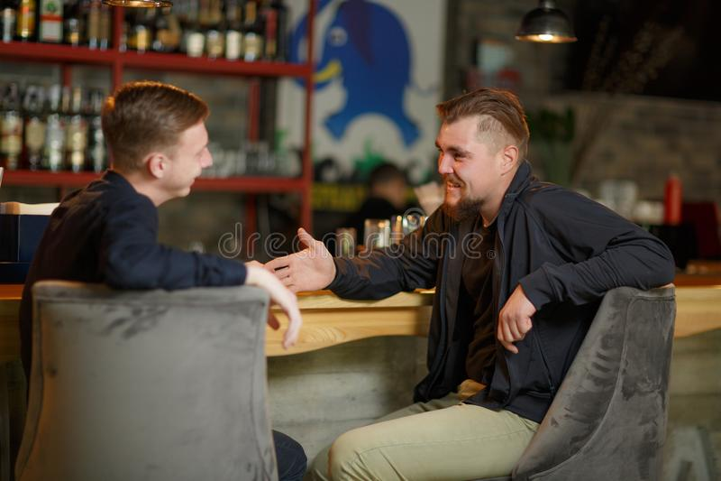 Deux hommes gais des amis s'asseyent dans une barre à la barre et parlent de quelque chose riant photos stock