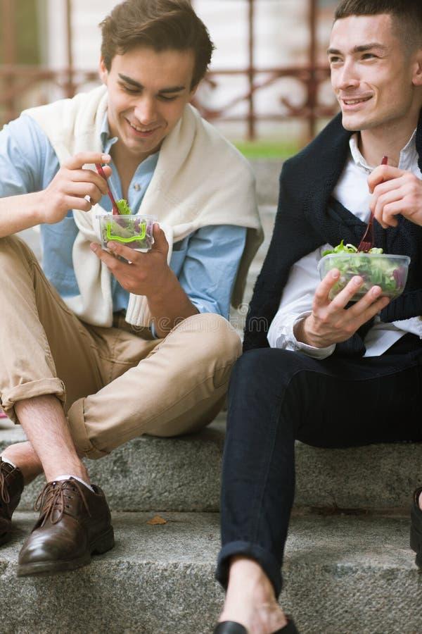 Deux hommes heureux avec la nourriture saine dehors image stock