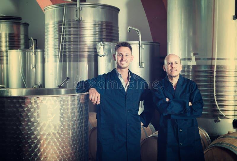 Deux hommes heureux dans des uniformes se tenant dans la fermentation d'établissement vinicole compar images libres de droits