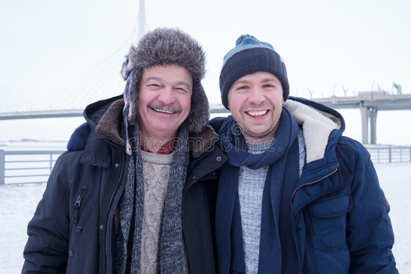 Deux hommes mûrs engendrent et fils habillé dans des vêtements chauds sniling et regardant la caméra photographie stock libre de droits