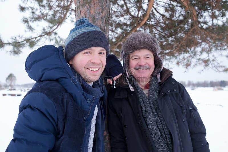 Deux hommes mûrs engendrent et fils habillé dans des vêtements chauds sniling et regardant la caméra images stock