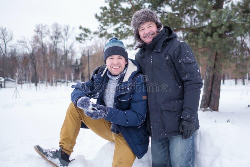 Deux hommes mûrs engendrent et fils habillé dans des vêtements chauds sniling et regardant la caméra photographie stock