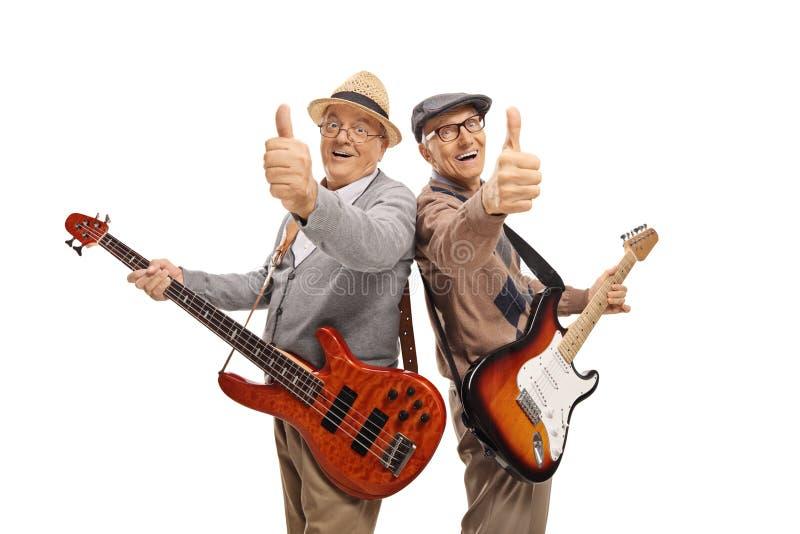 Deux hommes pluss âgé avec les guitares électriques montrant des pouces  images libres de droits
