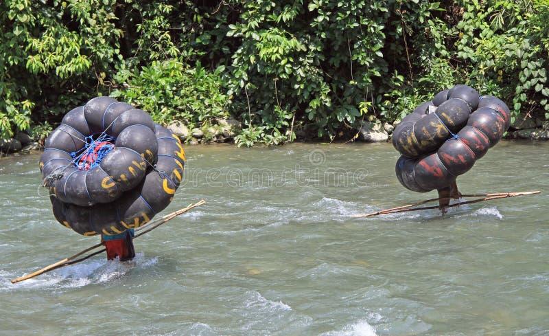 Deux hommes portent le tube, Bukit Lawang photographie stock