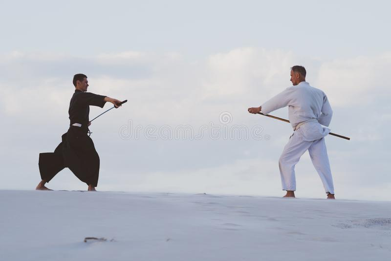 Deux hommes pratiquant des arts martiaux japonais dans le désert images libres de droits