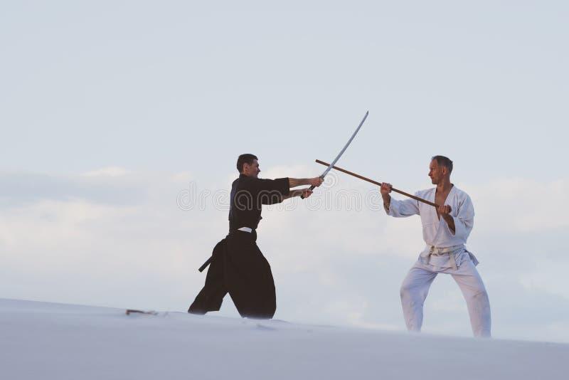 Deux hommes pratiquant des arts martiaux japonais dans le désert photo stock