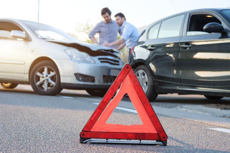 Deux hommes rapportant un accident de voiture pour la déclaration de sinistre image libre de droits