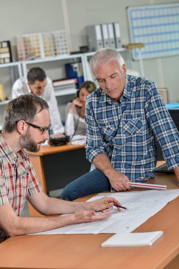 Deux hommes regardant les modèles un se sont assis sur la table images libres de droits