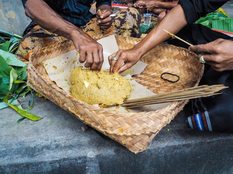 Deux hommes rendant le Balinese traditionnel satay dans un temple local dans U images stock