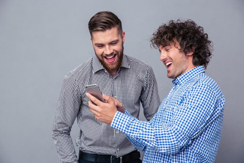 Deux hommes riants à l'aide du smartphone photo stock