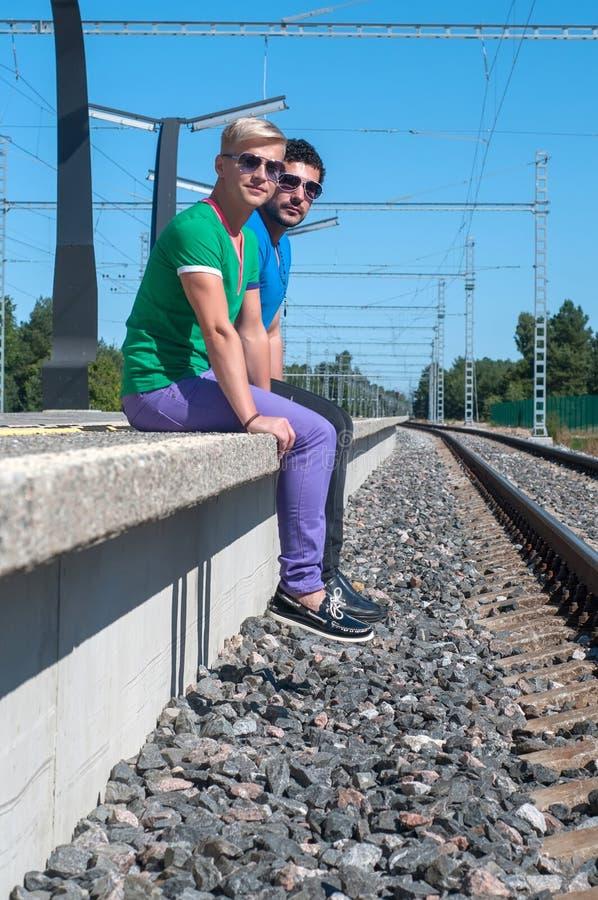 Deux hommes s'asseyant sur la plate-forme image stock