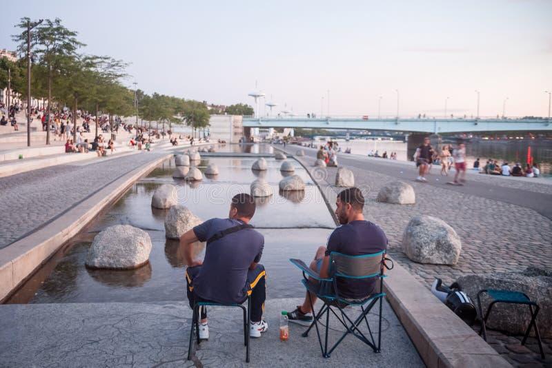 Deux hommes s'asseyant sur la rive des quais du Rhône faisant face au pont de Pont de la Guillotiere le soir photographie stock