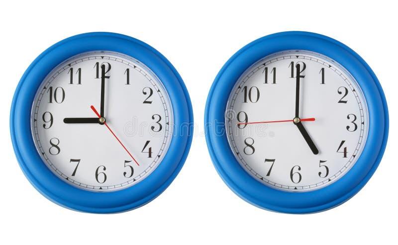 Deux horloges, une sur 9am et une sur 5pm. photos stock