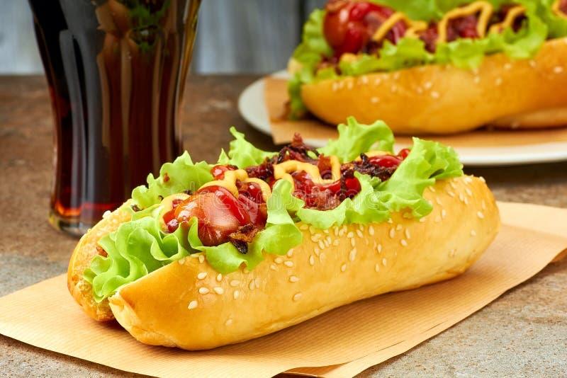 Deux hot-dogs avec les écrimages et le verre de kola image libre de droits