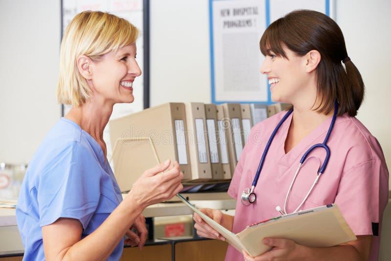 Deux infirmières discutant les notes patientes à la gare d'infirmières photographie stock