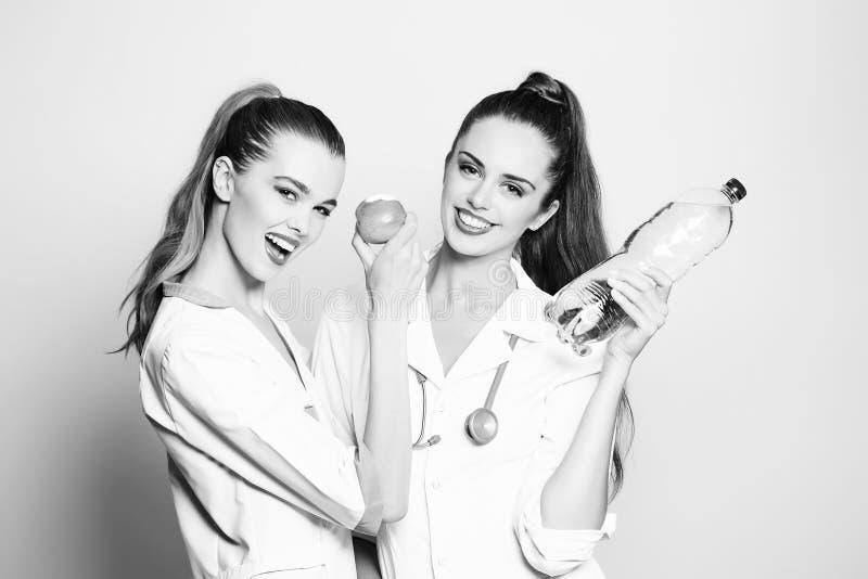 Deux infirmières heureuses de filles souriant avec les dents blanches saines sourient photos stock