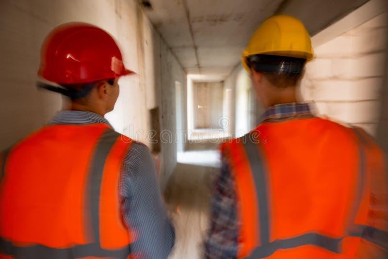 Deux ingénieurs civils habillés dans les gilets et les casques oranges de travail marchent à l'intérieur du bâtiment en construct images libres de droits