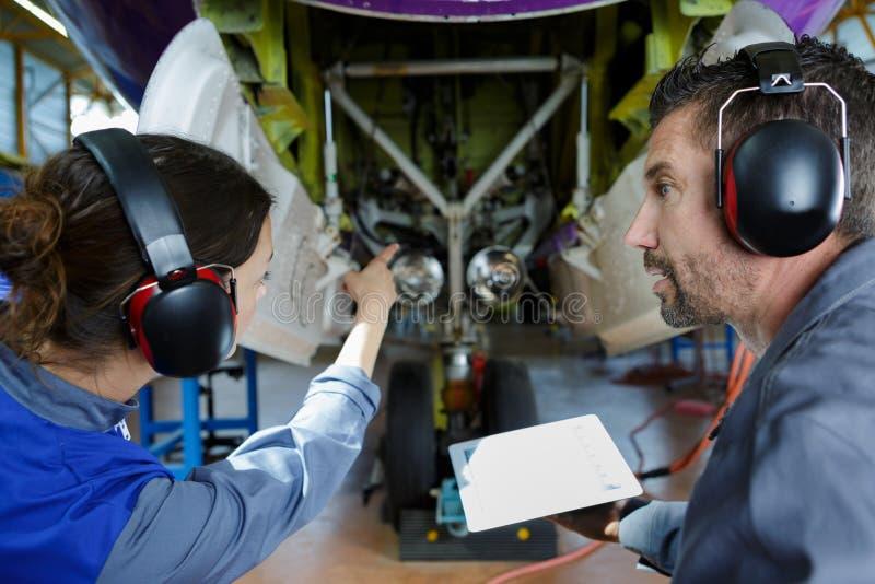 Deux ing?nieurs modernes d'avions regardant l'avion images stock