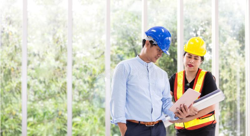Deux ingénieurs travaillant dehors avec un comprimé Deux travailleurs observent le plan de construction au bureau Affaires asiati image stock