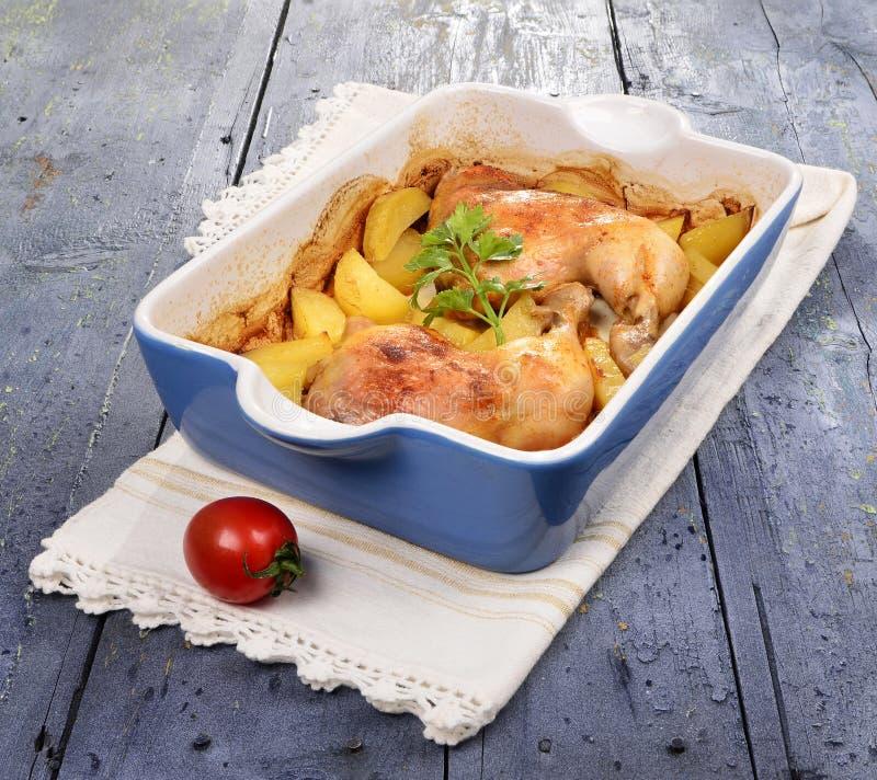 Deux jambes de poulet rôti avec la pomme de terre et l'épice verte fraîche dans un plateau images stock