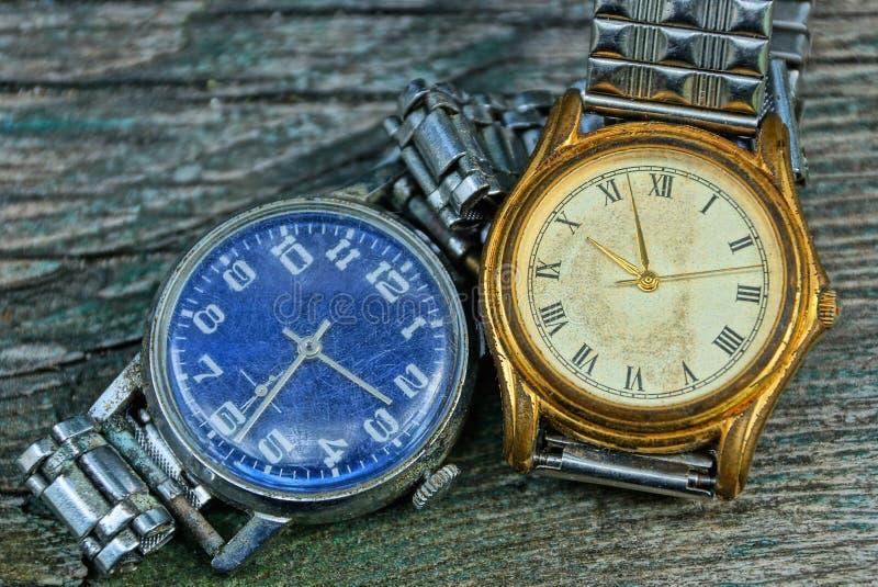 Deux jaunes et vieille montre minable bleue avec une courroie en métal images stock