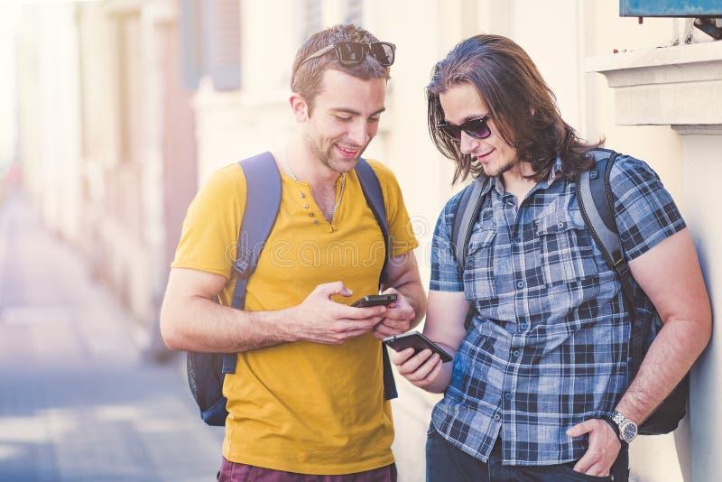 Deux jeune homme, amis intimes comparant des téléphones image stock
