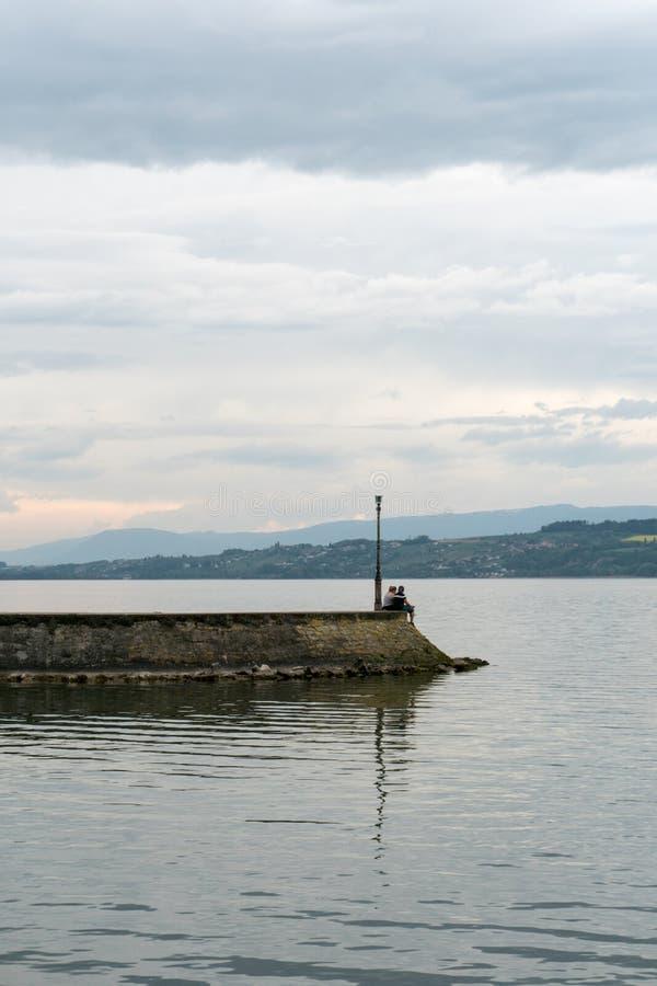 Deux jeunes amants à l'extrémité d'un long pilier regardant fixement au-dessus d'un lac photographie stock libre de droits