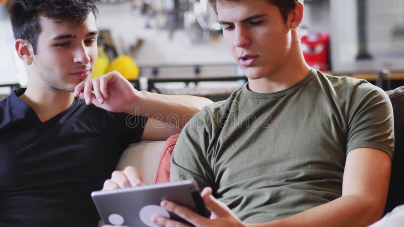 Deux jeunes amis masculins à l'aide de la tablette photo libre de droits