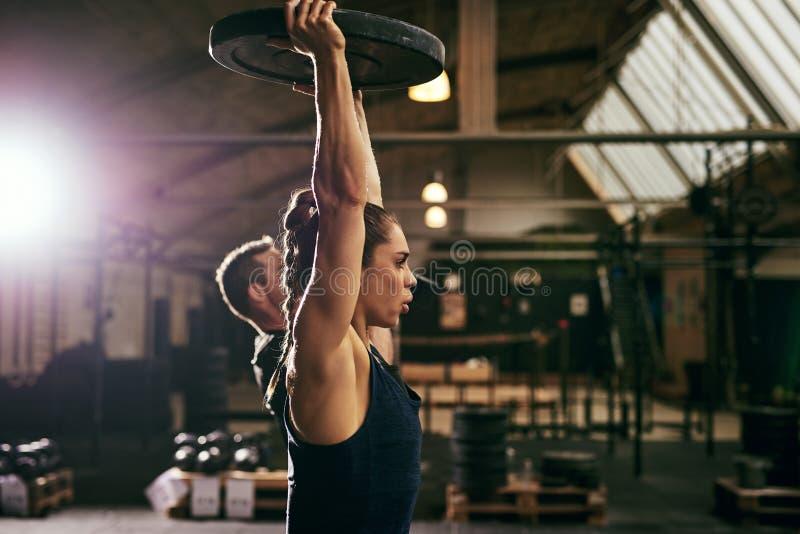 Deux jeunes athlètes folâtres s'exerçant avec des poids photographie stock