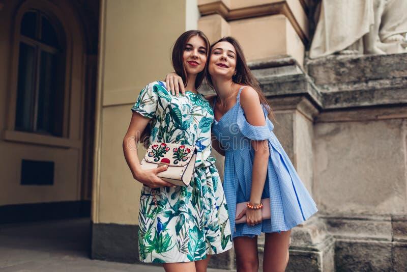Deux jeunes belles femmes étreignant dehors Filles ayant l'amusement dans la ville Les meilleurs amis traînent images stock