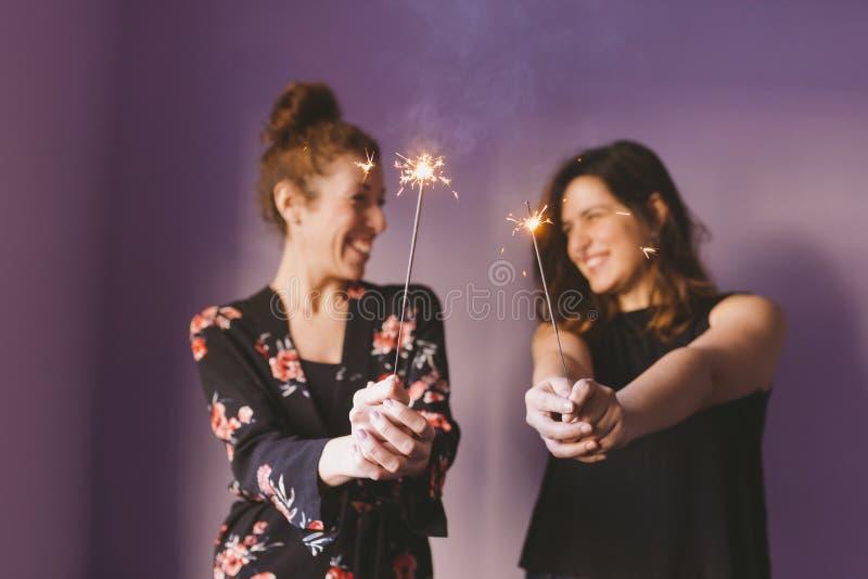 Deux jeunes belles femmes ayant l'amusement avec des étincelles à l'intérieur Fond pourpre Vêtement occasionnel Amusement, bonheu photo libre de droits