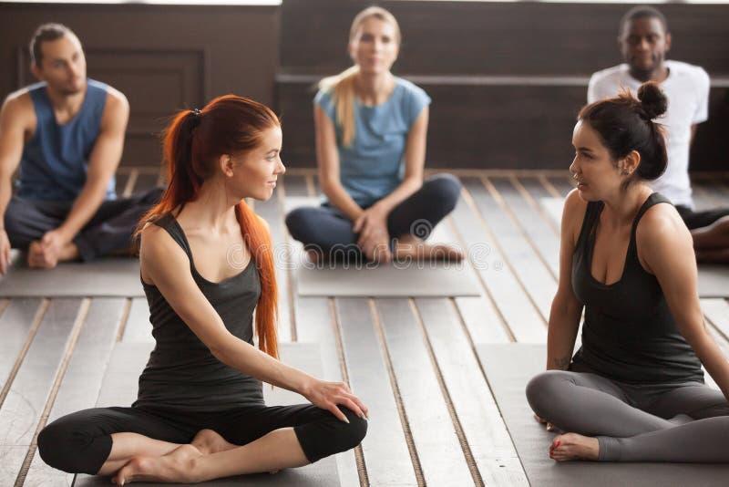 Deux jeunes belles femmes d'ajustement parlant à la formation de yoga de groupe image stock