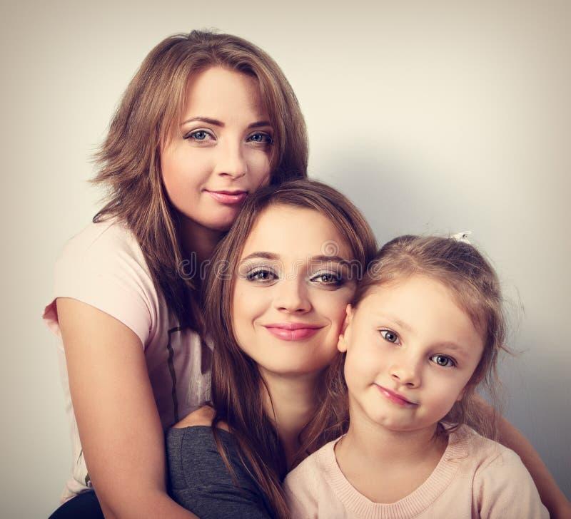 Deux jeunes belles femmes de sourire et fille heureuse d'enfant étreignant l'esprit image stock