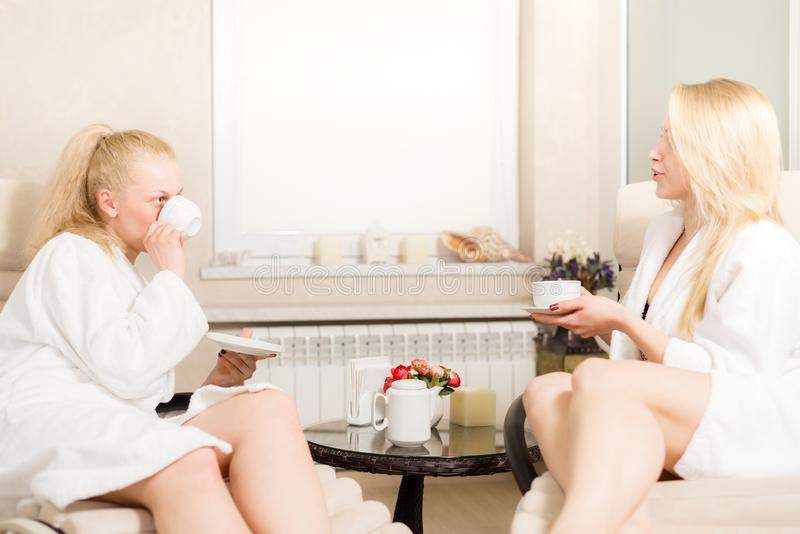 Deux jeunes belles filles dans le salon de station thermale les femmes blondes sont thé mignon et café parlants et potables photographie stock
