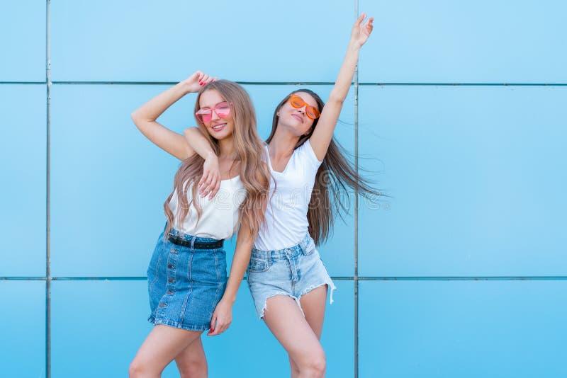 Deux jeunes belles filles de sourire de hippie dans des lunettes de soleil au néon colorées d'été à la mode Femmes insouciantes s photo libre de droits