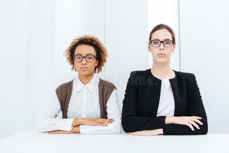 Deux jeunes busimesswomen sérieux en verres se reposant directement photos stock