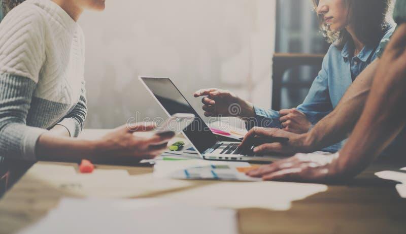 Deux jeunes collègues travaillant sur l'ordinateur portable dans le bureau Femme tenant le smartphone et se dirigeant sur l'écran photo stock