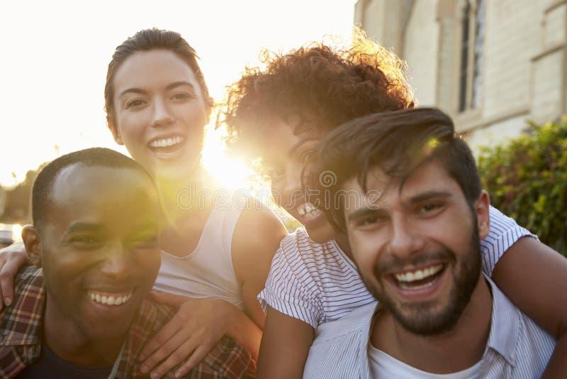 Deux jeunes couples adultes heureux ferroutant la rue photographie stock