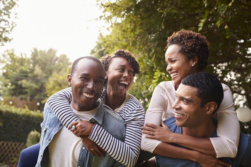 Deux jeunes couples noirs adultes ayant le ferroutage d'amusement photo stock