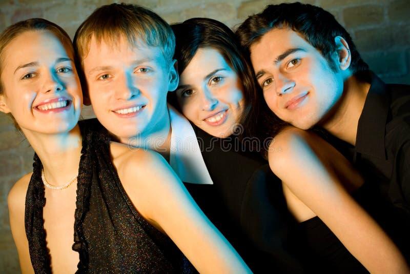 Deux jeunes couples ou amis de sourire attirants à une réception photo libre de droits