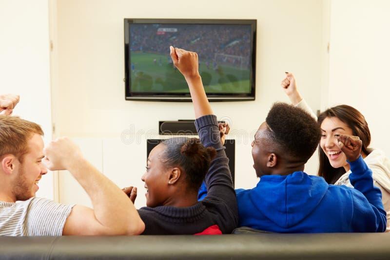 Deux jeunes couples regardant la télévision à la maison ensemble image stock