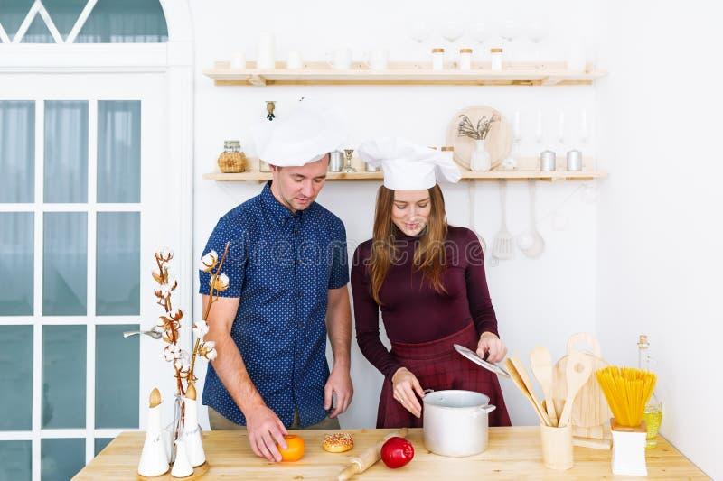 Deux jeunes cuisiniers heureux dans des chapeaux blancs font cuire la nourriture dans la cuisine image libre de droits