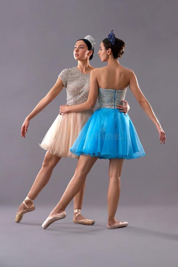 Deux jeunes danseurs classiques posant ensemble sur le fond gris photos stock