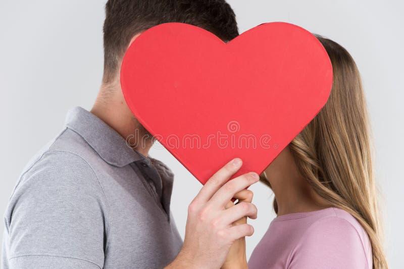 Deux jeunes dates derrière le coeur avec leurs visages de près d'un des autres photo stock