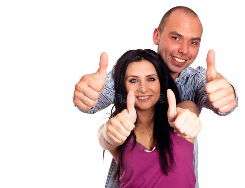 Deux jeunes de sourire avec des pouces- font des gestes d'isolement sur le petit morceau image stock