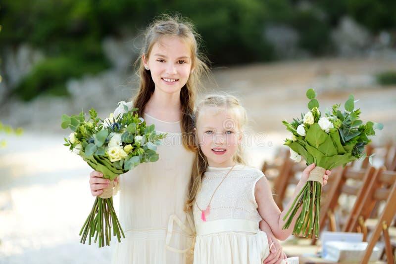 Deux jeunes demoiselles d'honneur adorables tenant de beaux bouquets de fleur après avoir épousé l'extérieur cemerony image libre de droits