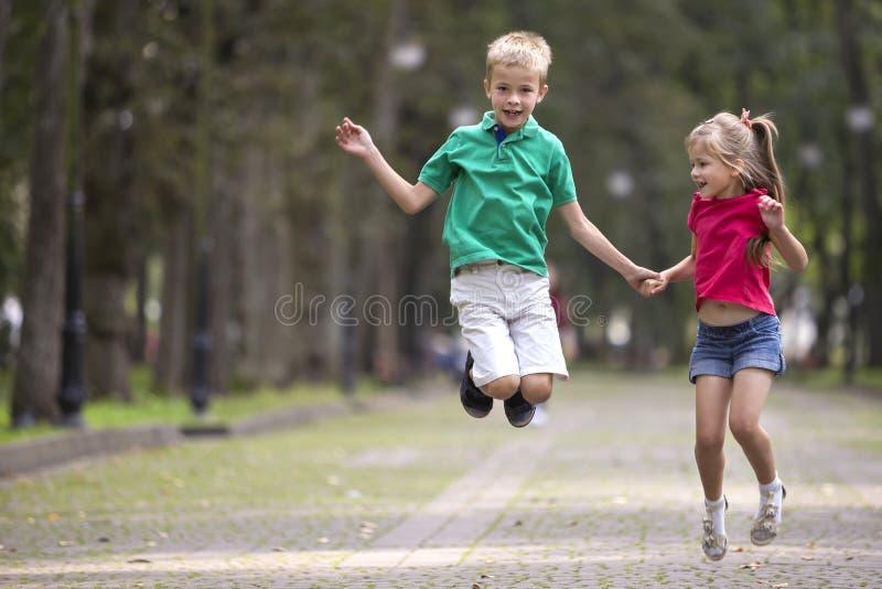Deux jeunes enfants de sourire drôles mignons, fille et garçon, frère et soeur, sautant et ayant l'amusement sur l'allée ensoleil image stock