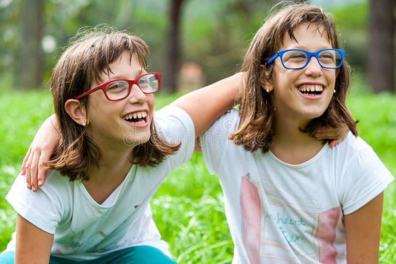 Deux jeunes enfants handicapés riant dehors. photo stock